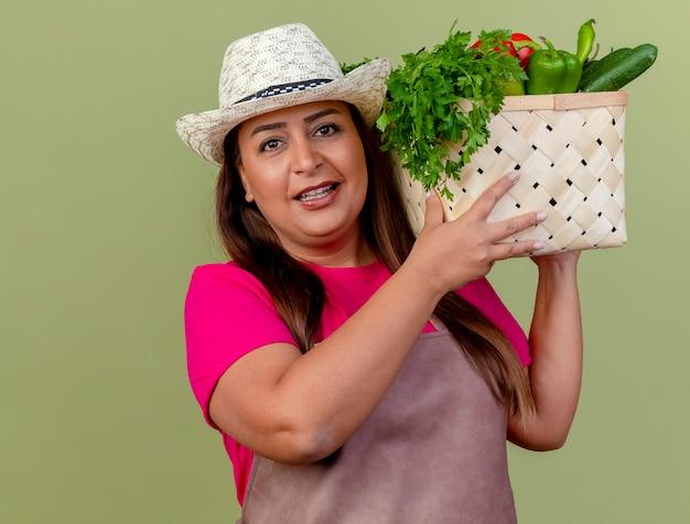 Женщина-садовник средних лет в фартуке и шляпе держит ящик, полный овощей