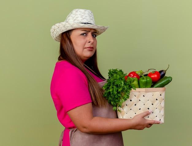 야채 가득한 상자를 들고 앞치마와 모자에 중간 세 정원사 여자