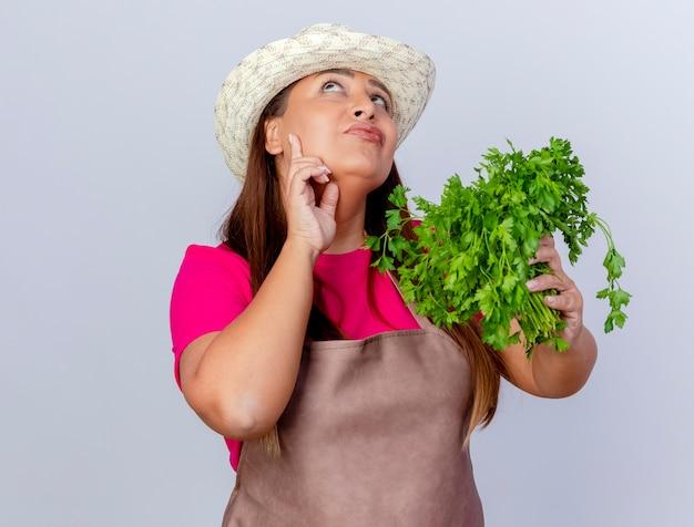 エプロンと帽子をかぶった中年の庭師の女性が白い背景の上に立って困惑して見上げる新鮮なハーブを保持しています