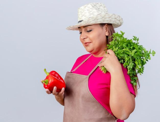 Женщина-садовник средних лет в фартуке и шляпе держит свежий красный болгарский перец и травы, глядя на перец с улыбкой на лице, стоя на белом фоне