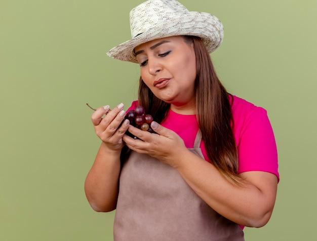 Женщина-садовник средних лет в фартуке и шляпе держит виноград