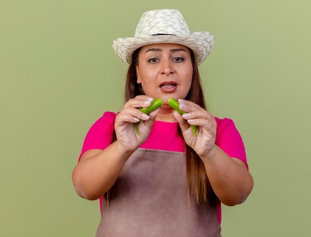 明るい背景の上に立って混乱しているように見える緑唐辛子の半分を保持しているエプロンと帽子の中年の庭師の女性