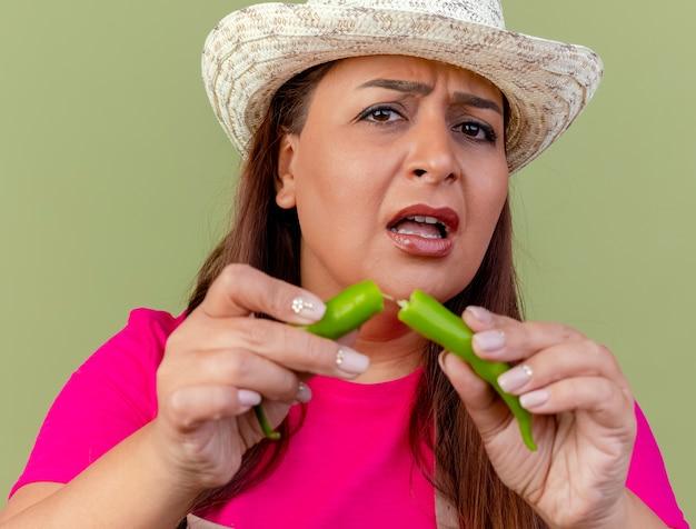 緑の唐辛子の半分を保持しているエプロンと帽子の中年の庭師の女性