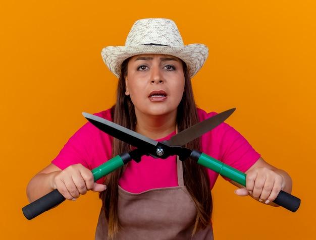 オレンジ色の背景の上に立って心配しているカメラを見ているヘッジクリッパーを保持しているエプロンと帽子の中年の庭師の女性