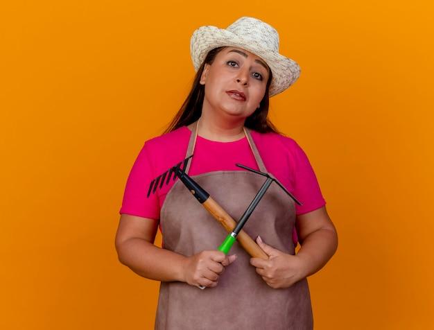 Женщина-садовник средних лет в фартуке и шляпе, держащая мотыгу и мини-грабли, смотрит в камеру с улыбкой на лице, стоя на оранжевом фоне