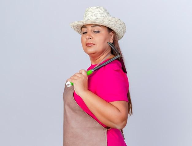 エプロンと帽子をかぶった中年の庭師の女性が自信を持ってマトックを持っている