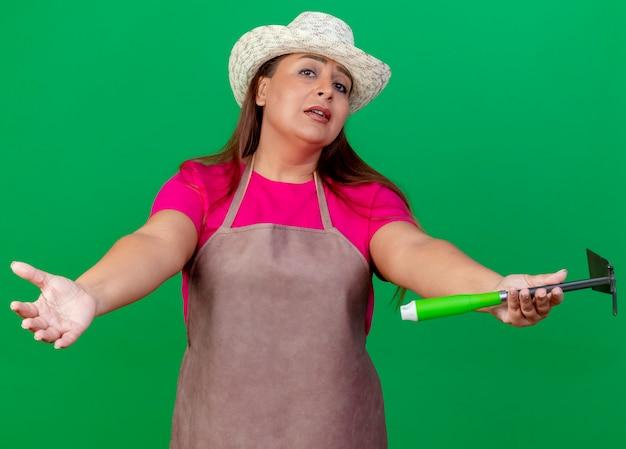 환영 제스처를 만드는 mattock을 들고 앞치마와 모자에 중간 세 정원사 여자