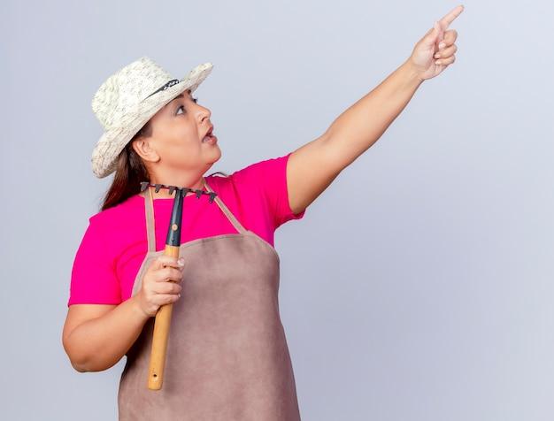 エプロンと帽子をかぶった中年の庭師の女性がマトックを持ち、人差し指で何かを驚かせている