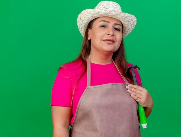 自信を持って笑顔のマトックを保持しているエプロンと帽子の中年の庭師の女性