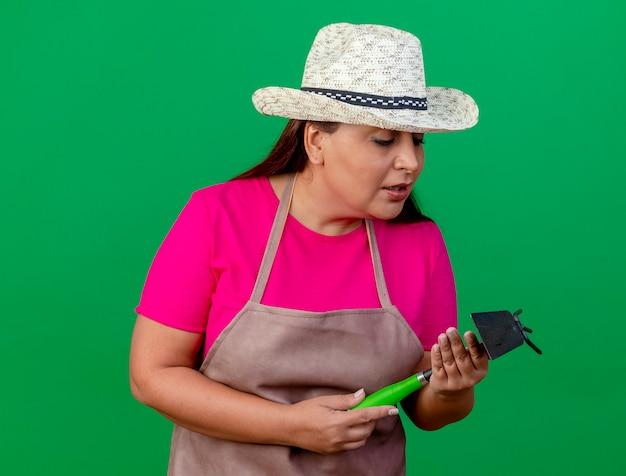 エプロンと帽子をかぶった中年の庭師の女性