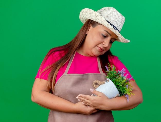 笑顔の赤ちゃんのように鉢植えの植物を保持しているエプロンと帽子の中年庭師の女性