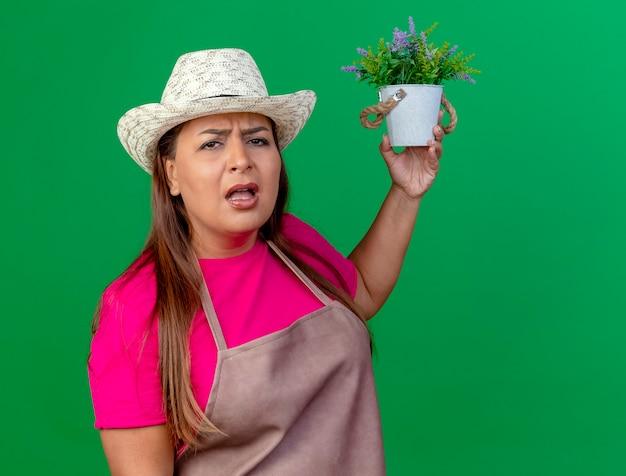 鉢植えの植物を保持しているエプロンと帽子の中年の庭師の女性