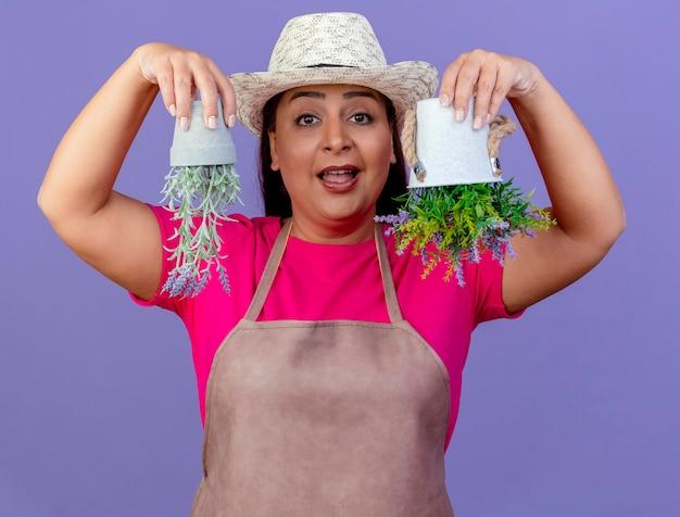 화분에 심은 식물을 들고 앞치마와 모자에 중간 세 정원사 여자