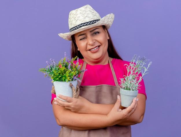 Женщина-садовник средних лет в фартуке и шляпе держит горшечные растения