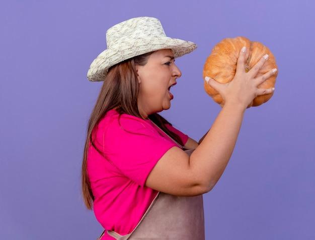 エプロンと帽子をかぶった中年の庭師の女性が紫色の背景に怒っている表情で叫んで横に立っているカボチャを保持しています