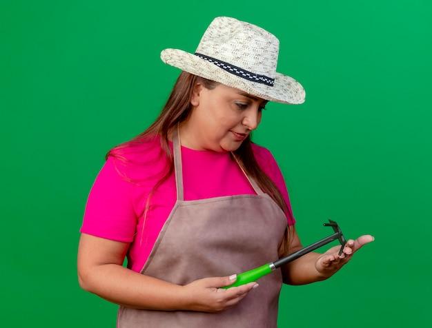 エプロンと帽子をかぶった中年の庭師の女性がマトックを見て