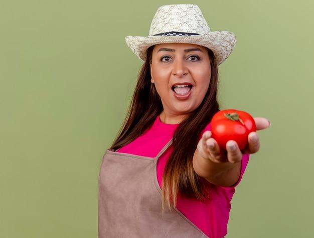 밝은 배경 위에 서 웃 고 카메라를보고 신선한 토마토를 제공하는 앞치마와 모자에 중간 세 정원사 여자