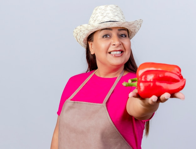 Женщина-садовник средних лет в фартуке и шляпе показывает свежий красный перец, весело улыбаясь, стоя на белом фоне