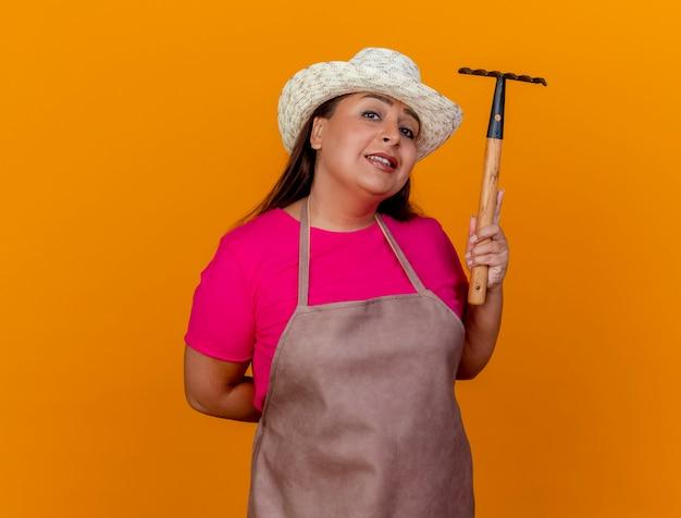 Женщина-садовник средних лет в фартуке и шляпе показывает счастливые и позитивные улыбающиеся мини-грабли на оранжевом фоне