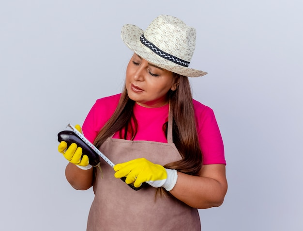 앞치마와 흰색 배경 위에 테이프 측정 서와 함께 측정 신선한 가지를 들고 고무 장갑을 끼고 모자에 중간 세 정원사 여자