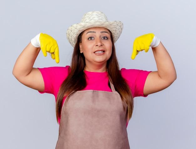 エプロンと帽子をかぶった中年の庭師の女性が白い背景の上に立って人差し指を下に向けてカメラの笑顔を見てゴム手袋を着用