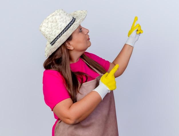 앞치마와 모자 흰색 배경 위에 서 심각한 얼굴로 검지 손가락으로 뭔가 가리키는 고무 장갑을 끼고 중간 세 정원사 여자