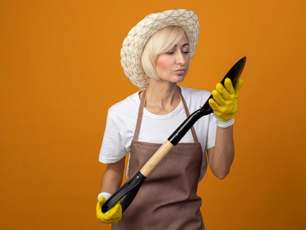 Женщина-садовник средних лет в униформе садовника в шляпе и садовых перчатках держит и смотрит на лопату, делая жест поцелуя