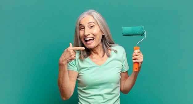 그녀의 벽을 장식 페인트 롤러와 중간 세 회색 머리 여자