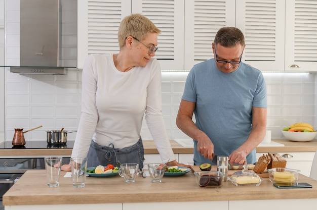 Middle aged husband helps his happy senior wife cooked dinner in kitchen wears casual clothes loving