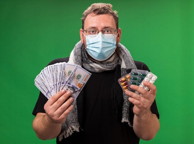 緑の壁に隔離された医療マスクとスカーフを身に着けている中年の病気の男性
