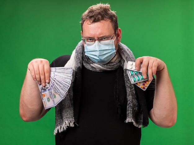 Больной мужчина средних лет в медицинской маске и шарфе изолирован на зеленой стене