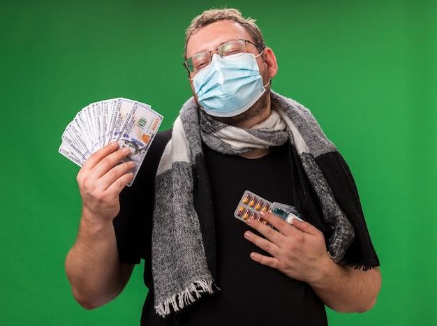 녹색 벽에 격리된 의료용 마스크와 스카프를 착용한 중년 남성