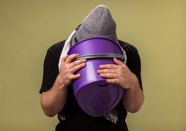 冬の帽子とスカーフを身に着けている中年の病気の男性がプラスチックのバケツを持ってそれに嘔吐している