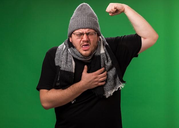 冬の帽子と緑の壁に隔離のスカーフを身に着けている中年の病気の男性