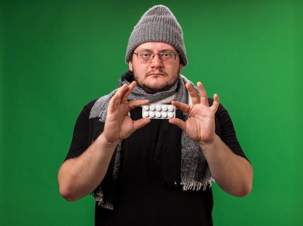 冬の帽子とスカーフを身に着けている中年の病気の男性-緑の壁に隔離