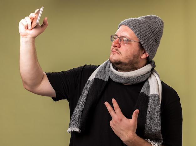 冬の帽子とスカーフを身に着けている中年の病気の男性は、平和のジェスチャーを示す自分撮りを取ります