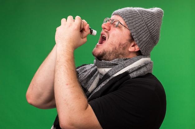 冬の帽子とスカーフを身に着けている中年の病気の男性-