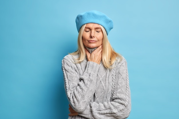 Middle aged ill woman touches neck suffers sore throat has flu symptom closes eyes to relieve pain stands unhappy indoor wears beret and warm knitted sweater. unpleasant feelings while swallow