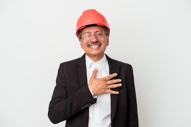 흰색 배경에 고립 된 중년 인도 건축가 남자는 가슴에 손을 잡고 큰 소리로 웃습니다.