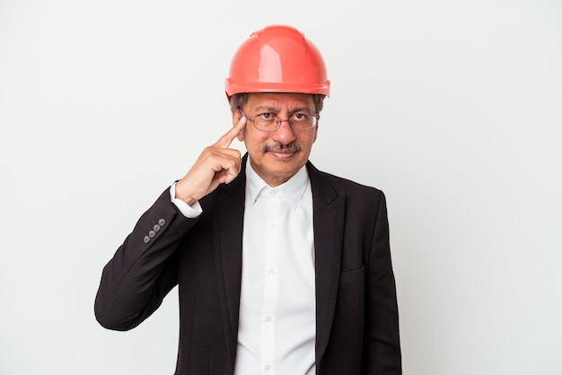 Middle aged indian architect man isolated on white background pointing temple with finger, thinking, focused on a task.