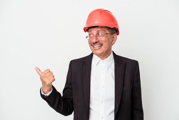 Middle aged indian architect man isolated on white background points with thumb finger away, laughing and carefree.