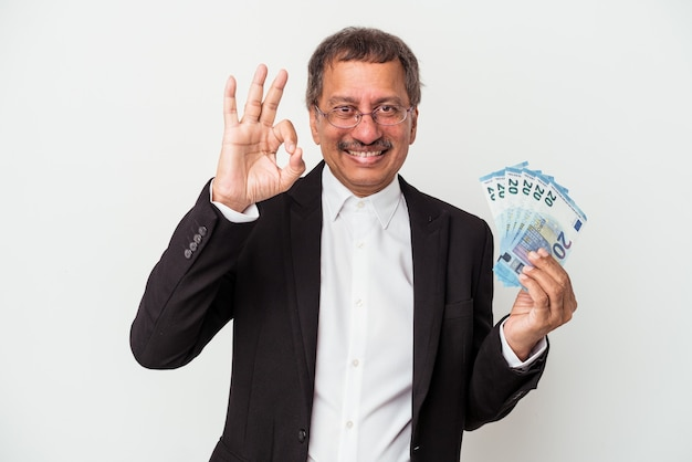 Middle aged indian business man holding bills isolated on white background cheerful and confident showing ok gesture.