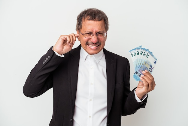 Middle aged indian business man holding bills isolated on white background covering ears with hands.