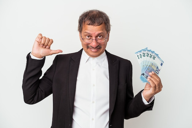 Middle aged indian business man holding bills isolated on white background feels proud and self confident, example to follow.