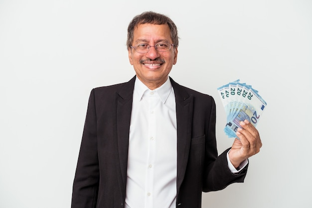 Middle aged indian business man holding bills isolated on white background happy, smiling and cheerful.