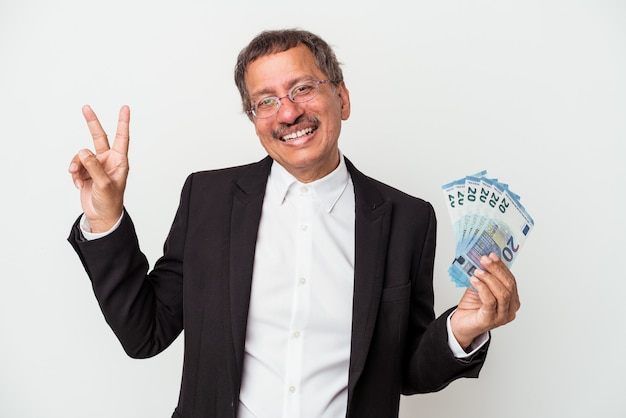 Middle aged indian business man holding bills isolated on white background joyful and carefree showing a peace symbol with fingers.