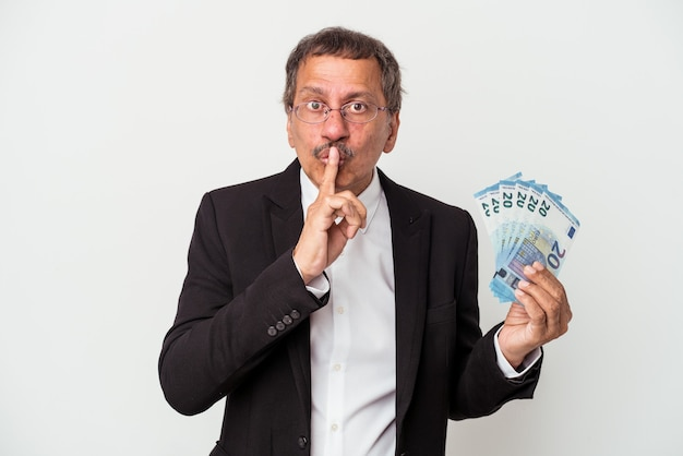 Middle aged indian business man holding bills isolated on white background keeping a secret or asking for silence.