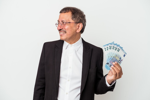 Middle aged indian business man holding bills isolated on white background looks aside smiling, cheerful and pleasant.