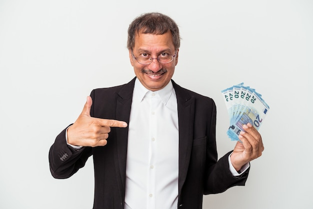 Middle aged indian business man holding bills isolated on white background person pointing by hand to a shirt copy space, proud and confident