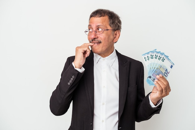 Middle aged indian business man holding bills isolated on white background relaxed thinking about something looking at a copy space.